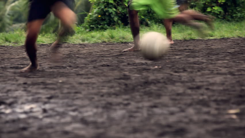 A Gang Of Bar Feet Kids Playing Soccer On A Muddy Field. Serial Of Slow Motion Shots With Depth Of Field Effects. Action Loaded Details Of Running Legs And ...
