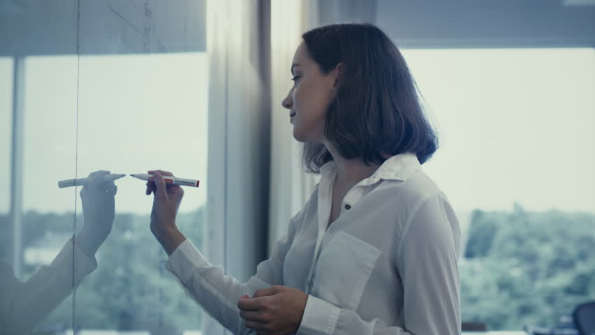 Young Female Office Worker in White Shirt is Writing on Glass Whiteboard. Shot on RED Cinema Camera in 4K (UHD). | Shutterstock HD Video #11917658
