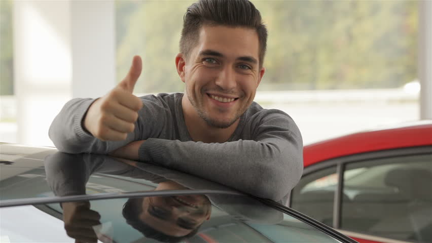 The buyer of the car shows the thumbs up. Auto business, car sale, technology and people concept - happy male with car dealer in auto show or salon. Young man with a salesman in a motor show.