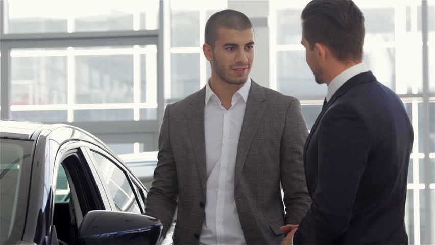 Car Showroom. Vehicle Dealer Showing Young Man New Car. Auto business, car sale, technology and people concept - happy male with car dealer in auto show or salon. Young man with a salesman in a motor