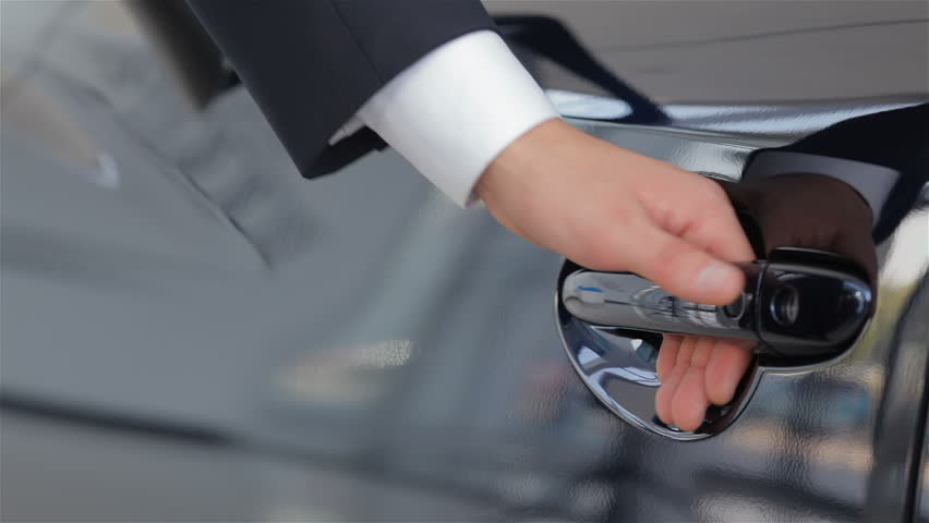 Close up human hand opening car door. Auto business, car sale, technology and people concept - happy male with car dealer in auto show or salon. Young man with a salesman in a motor show.