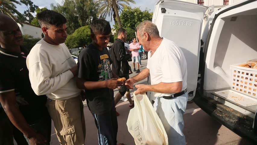 KOS, GREECE - SEP 27, 2015: War refugees receive humanitarian assistance - bread. More than half are migrants from Syria, but there are refugees from other countries-Afghanistan, Pakistan, Iraq, Iran.