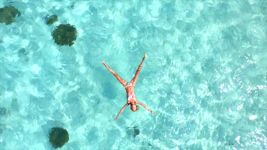 AERIAL SLOW MOTION: Beautiful young woman swimming, lying on a water surface in crystal clear ocean #11925161