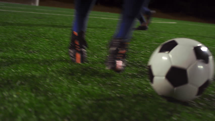 A female soccer player dribbles down the field during a game at night #11951426