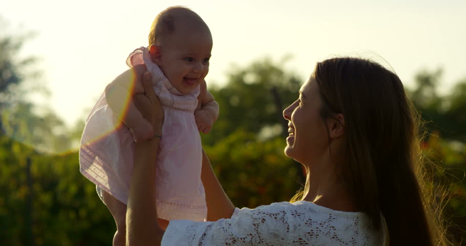Super slow motion of young Caucasian mother and baby girl enjoy their happy moments together  in a meadow of vineyard on a sunshine in 4k (close up with flares) #11958467