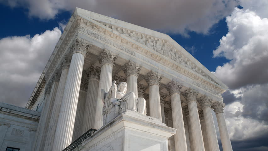 Supreme Court building in Washington DC with time lapse clouds.