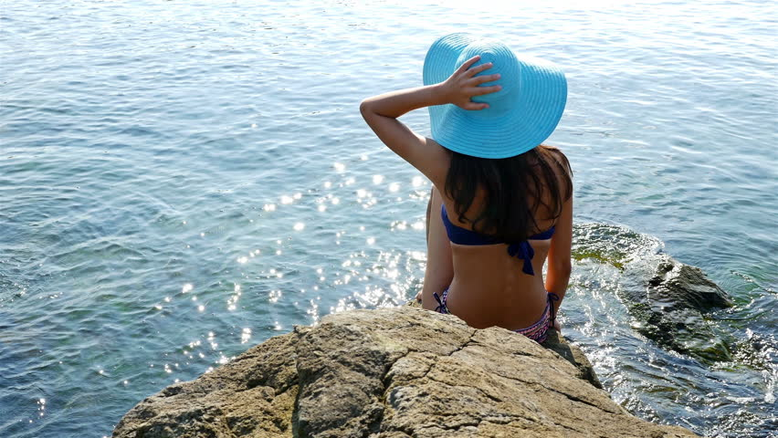 Young woman in swimming suit and blue hat sitting on rocks on the sea shore #11964293