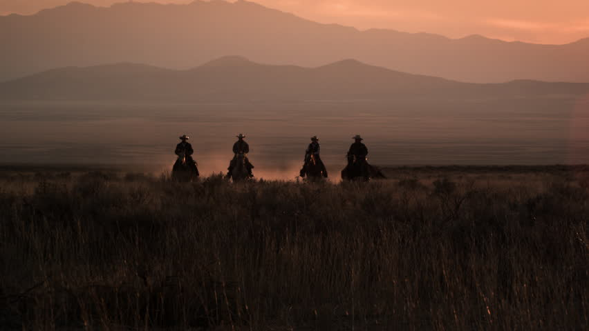 Four cowboys galloping in distance with hazy mountain range and pink sunset. Dust is visible behind horses.