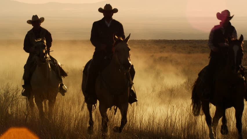 Silhouetted cowboys galloping together in a line in slow motion, Dusk kicks up as they ride. Golden hour with sun lens flare.