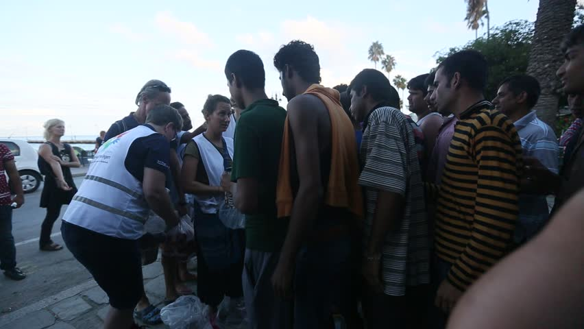 KOS, GREECE - SEP 28, 2015: War refugees stand in a queue to receive humanitarian aid - water and apples. Part are migrants from Syria, but there are refugees from other countries.