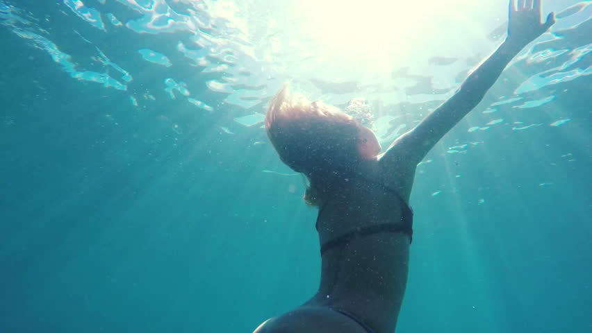 Woman in Bikini swimming underwater towards surface with beautiful sun flares in slow motion. Instagram Color Tone