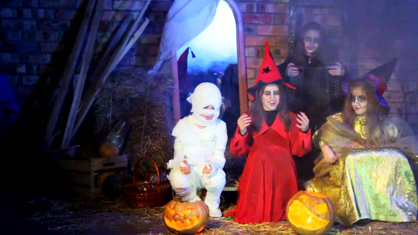 Three little witches and ghost are singing a song, playing accordion and broom and having fun at Halloween party in the room decorated for this holiday.