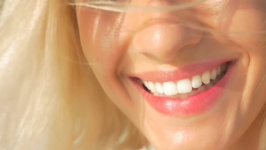 SLOW MOTION CLOSE UP: Beautiful young woman with perfect white teeth starts laughing