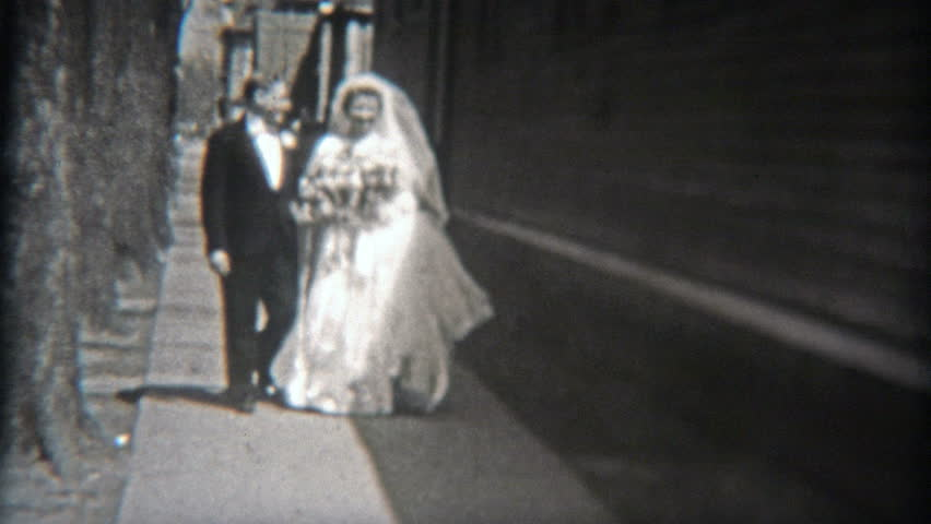 BALTIMORE, MARYLAND 1942: Happy wedding couple walking outside before ceremony.