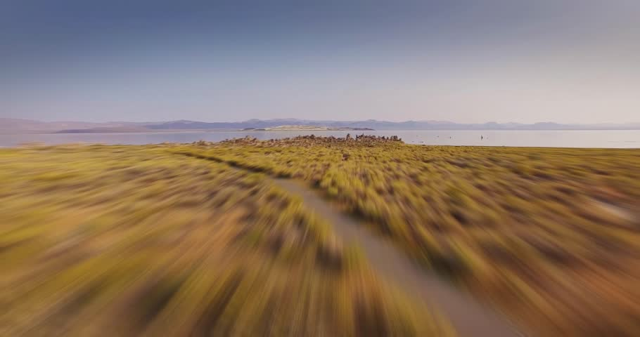 Fast low altitude POV aerial flight over desert landscape toward beautiful Mono Lake, California. 4K UHD.