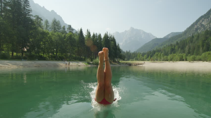 SLOW MOTION CLOSE UP: Young brunette woman in bikini jumping over the camera and diving into the beautiful mountain lake in sunny summer
