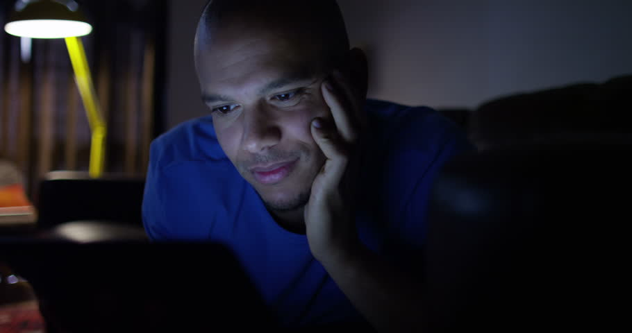 An attractive young man streaming a movie on his digital tablet. Shot on RED Epic.
