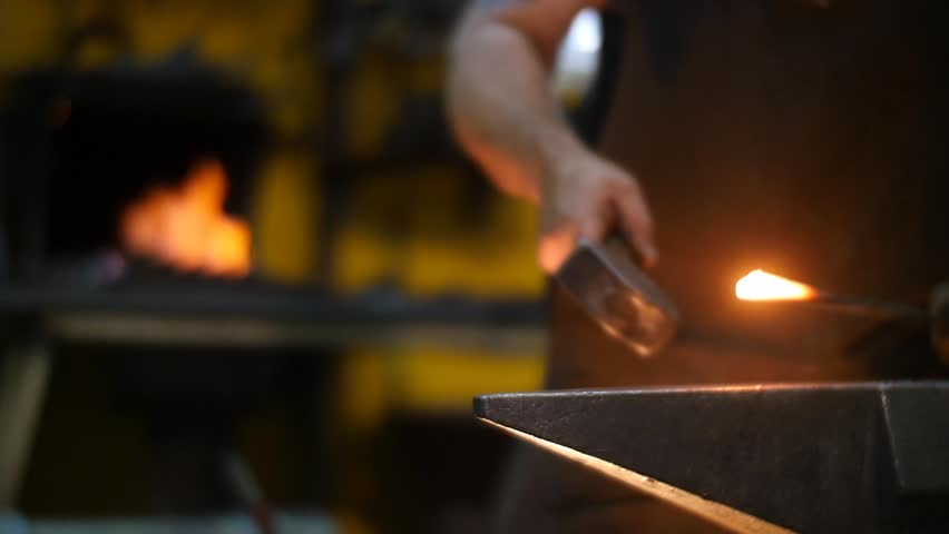 Blacksmith Forging Sword with Sparks in a Workshop Slow Motion