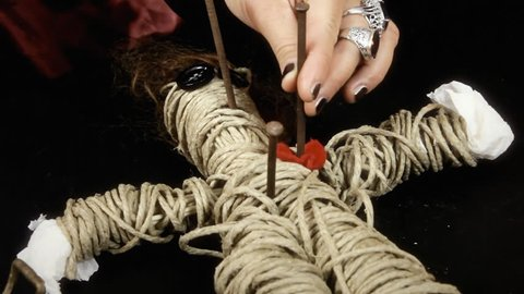 A witch hammering nails in the body of a voodoo doll (heart-shaped fabric). Close-up shot.
