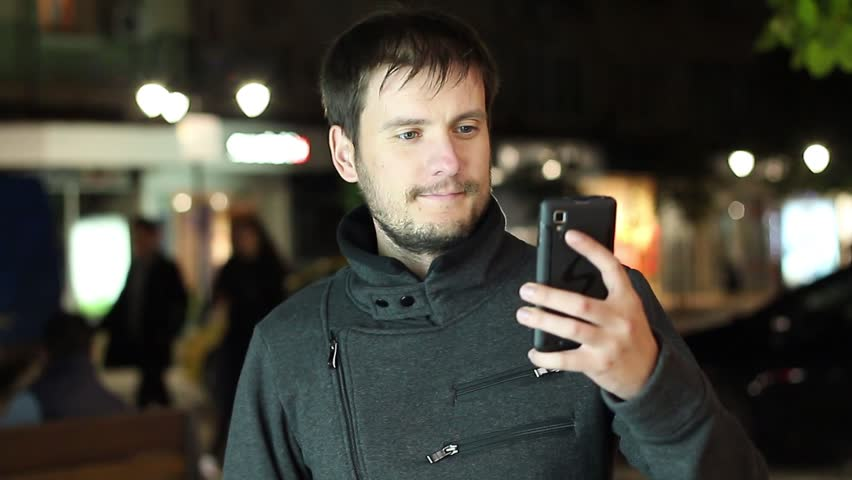 Bearded man with phone makes selfie in city | Shutterstock HD Video #12028445