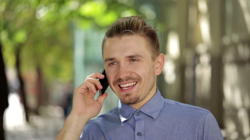 A very handsome man is talking on his smartphone | Shutterstock HD Video #12039731