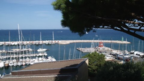 Italy - October, 2012: Wide shot of an ocean harbor and a hotel swimming pool