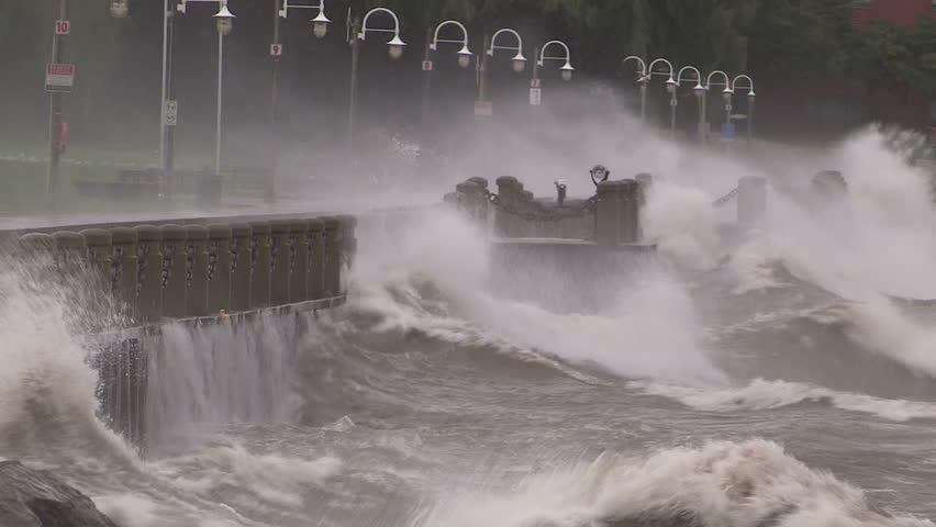 Huge powerful waves breaking at seawall in major severe storm.