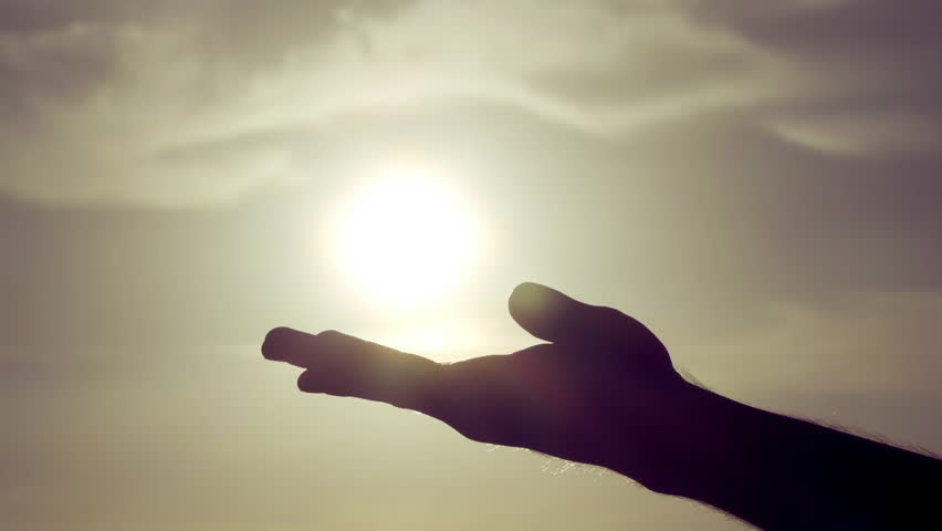 Grasping the sun with palm/fingers slow motion.100fps-25fps conformed slow motion shot of a silhouetted male hand against a sun and sky background, grasping the sun and letting sunlight pass through.