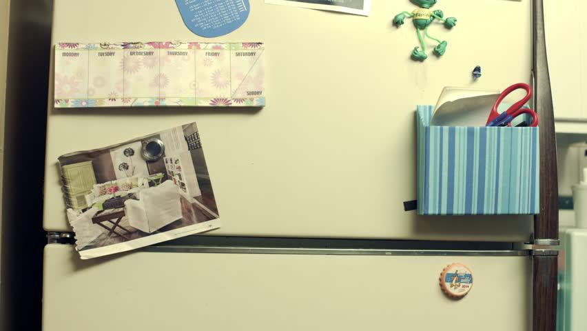 Student / son posting school test grade on refrigerator.