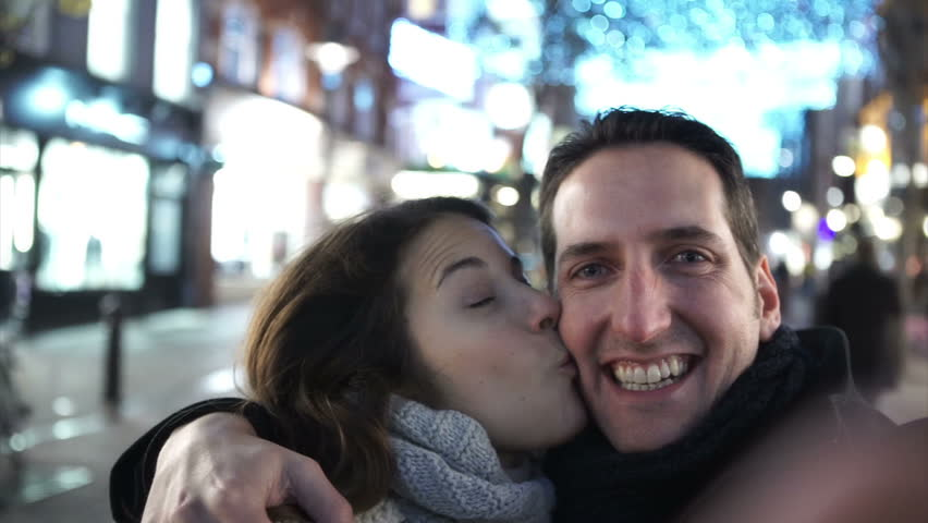 Fun couple in the city at night taking a selfie, as seen from the camera's p.o.v. Shot on RED Epic.