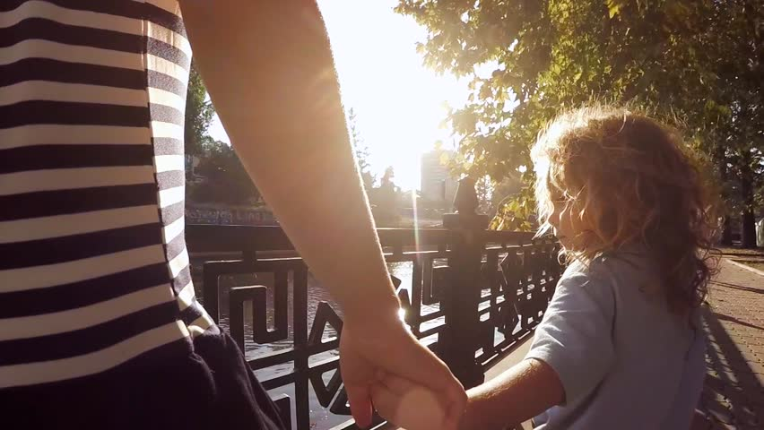 SLOW MOTION.  Little boy and girl 11 years walking in a city park along the river. Children hold hands and through Handshake seen sunlight. The camera moves for the kids.  | Shutterstock HD Video #12135281