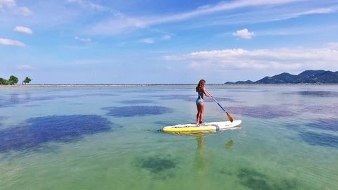 Stand up paddle board woman paddleboarding on SUP on Samui Thailand standing happy on paddleboard on in water. Young  female model on Thailand beach on summer holidays vacation