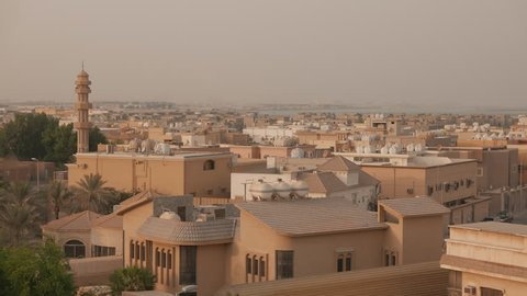 Middle East city view, late afternoon. Al Rakka, Saudi Arabia. Residential area with a mosque. Man in a traditional white outfit is seen on a balcony with his son.