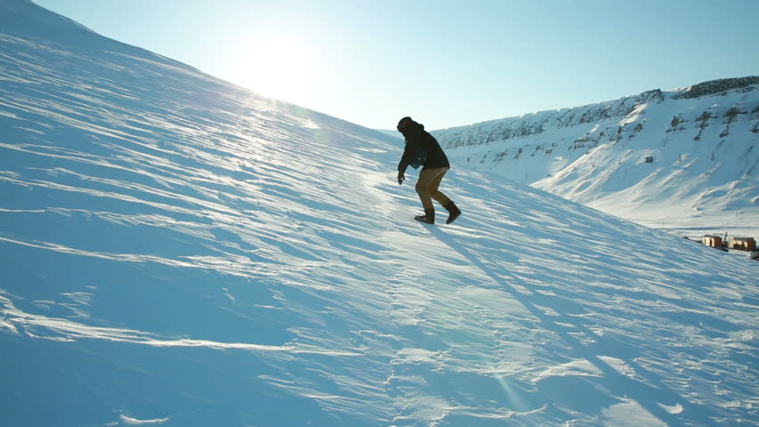 A man trying to climb the mountain on a slippery frozen snow, slips and falls.