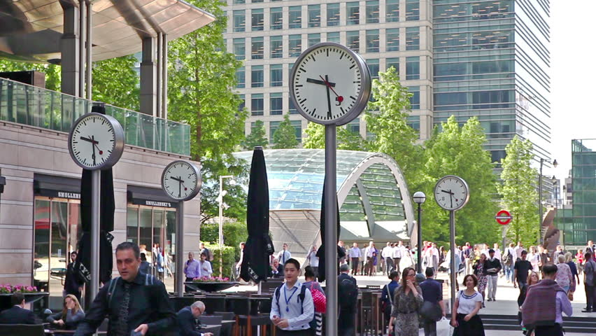 LONDON, UK - JULY 03, 2015: Commuters rushing to work in Canary Wharf. Lots of people passing the famous square with clocks | Shutterstock HD Video #12153647