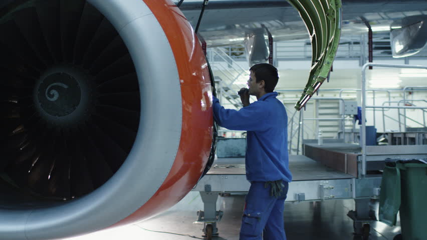 Aircraft maintenance mechanic with a flash light inspects plane engine in a hangar. Shot on RED Cinema Camera in 4K (UHD).