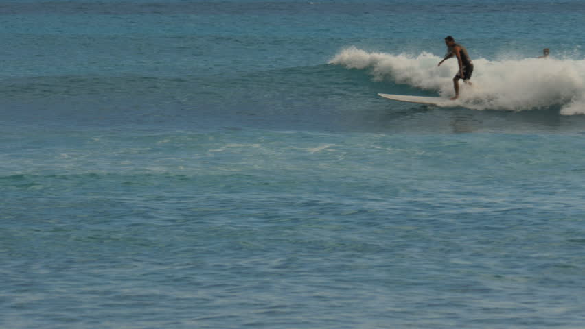 WAIKIKI, UNITED STATES OF AMERICA - AUGUST 9 2015: a man rides a longboard at waikiki beach, hawaii   Shutterstock HD Video #12181490