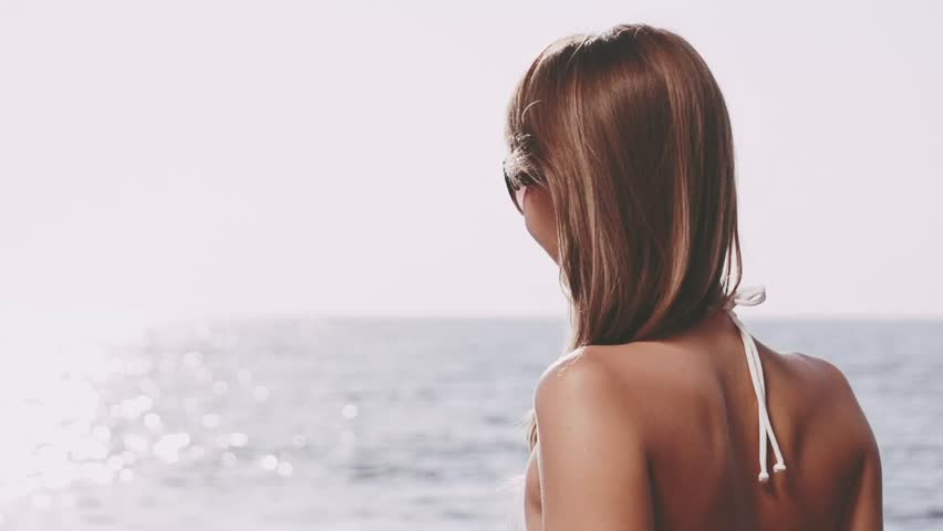 Beautiful young woman in bikini is styling her hair on the sea beach. Sunny summer by the sea. Slow motion. Filmed at 250 fps. | Shutterstock HD Video #12189761