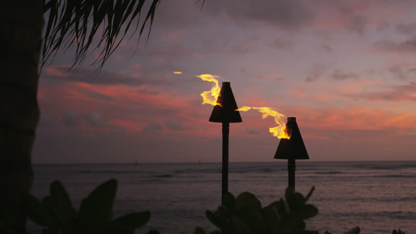 Torches with fire and flames burning in Hawaii sunset sky by palm trees. Beautiful slow motion torches on Hawaiian Waikiki beach, Oahu. RED EPIC SLOW MOTION   Shutterstock HD Video #12193856