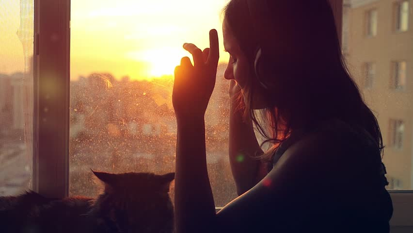 Young woman wears headphones and relaxing with her lovely Maine Coon cat at window with blurred city background at sunset in slowmotion. 1920x1080
