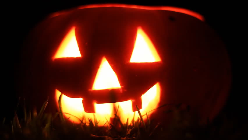Funny Halloween pumpkin face with glowing candle in Grass. Close Up. | Shutterstock HD Video #12214004
