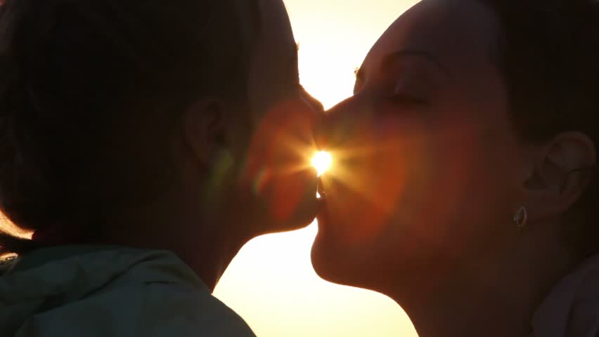 Silhouettes of mother and her daughter heads, daughter kisses mother | Shutterstock HD Video #1222360