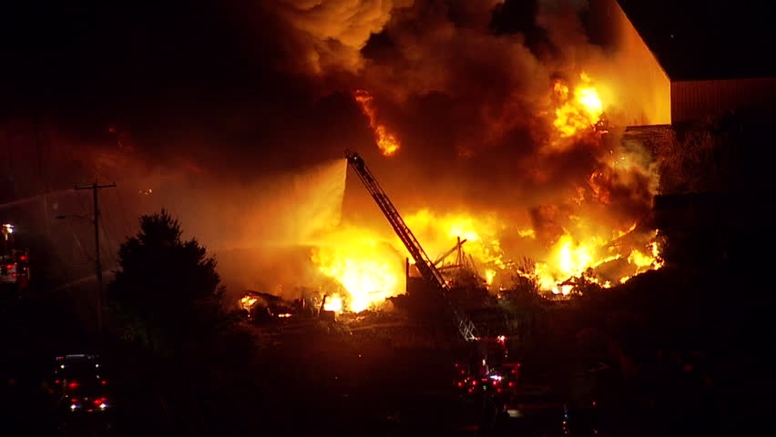 Night time aerial shot of a large building or warehouse fire. Fire department and emergency crews on scene to fight and extinguish the flames before the building is destroyed from wildfire spread. NX