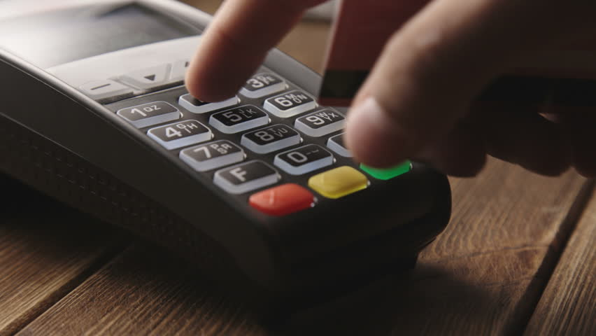 Man's hand pushing the button and swipe credit card payment on pos terminal standing on wooden desk. | Shutterstock HD Video #12236030