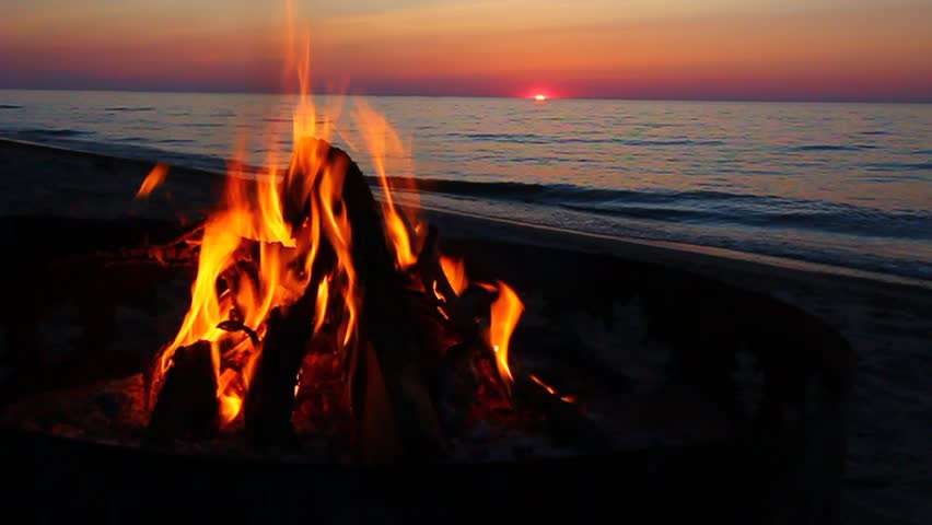 Campfire burns brightly at sunset along the beautiful beach of Lake Superior in northern Michigan | Shutterstock HD Video #1223728