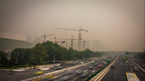 China's capital city of Beijing street traffic of automobiles. Foggy day, smog, air pollution.