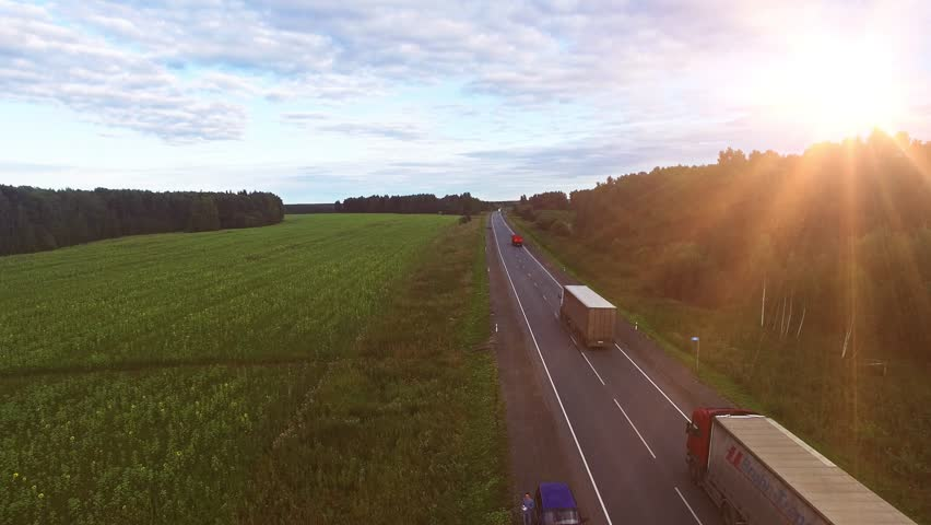 Aerial view of Truck on the road with sunset in the background. Large delivery truck is moving towards setting sun. #12250712