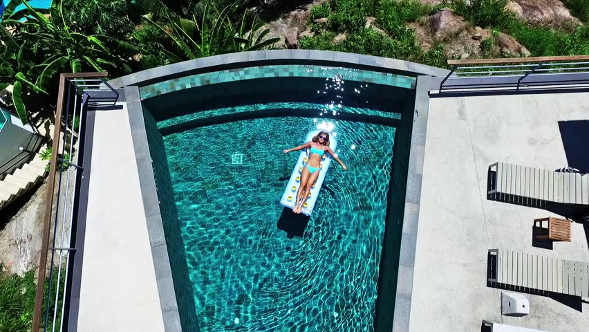 Young girl swims in the pool on an air mattress in sun glasses on Villa. Aerial view.