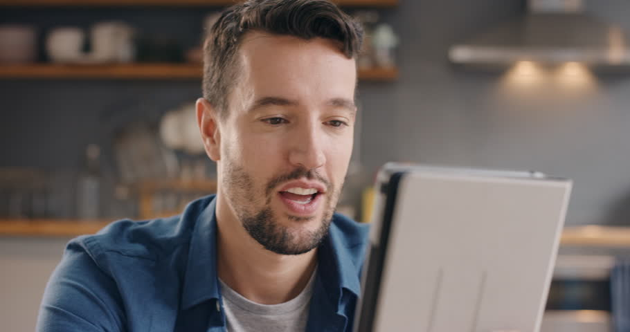 Happy man talking to his friend online having video chat using digital tablet app at home in kitchen | Shutterstock HD Video #12266246
