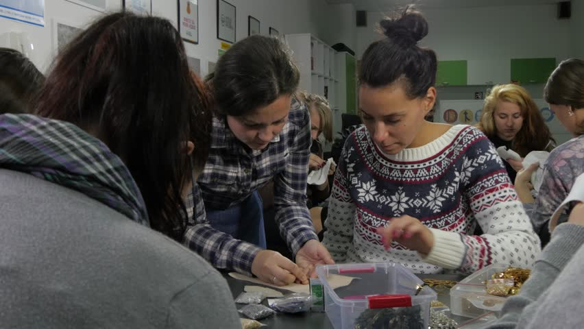 Creative workshop,women group of students watching female teacher which shows sewing  decorative elements like zircons or beads at drawn template,handmade,artistic skills,artwork,educational,interior. | Shutterstock HD Video #12266567